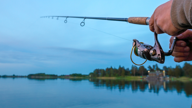 a fisherman's hands on the rod at the lake