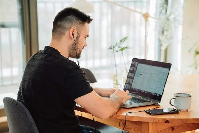 Hombre con playera negra, sentado en una silla gris, trabajando en una macbook que está sobre una mesa de madera