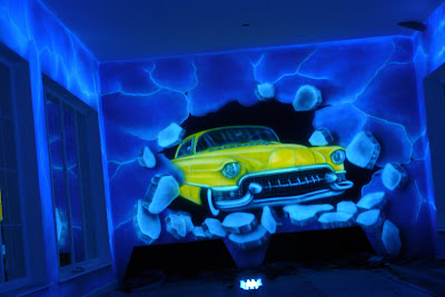 Malowidło ścienne przedstawiające samochód rozwalający ścianę, malowidło wykonane w kręgielni na ścianie. Warszawa
