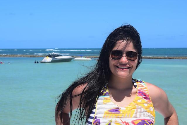 mulher de cabelo preto, pele branca e oculos esculos em uma lancha