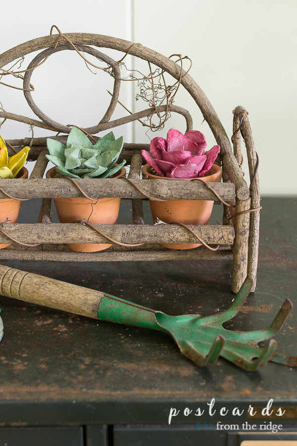 vintage garden hand rake and colorful flowers made from paper egg cartons
