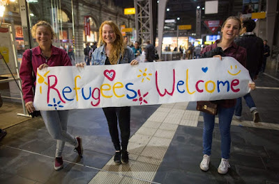 German girls welcoming Syrian refugees