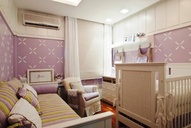 """Neste quarto de bebê o amarelo nos acessórios deu uma """"quebrada"""" em lilás produzindo uma combinação mais alegre. Destaque para as florzinhas estampadas nas paredes que podem ser facilmente reproduzidas com estêncil para parede."""