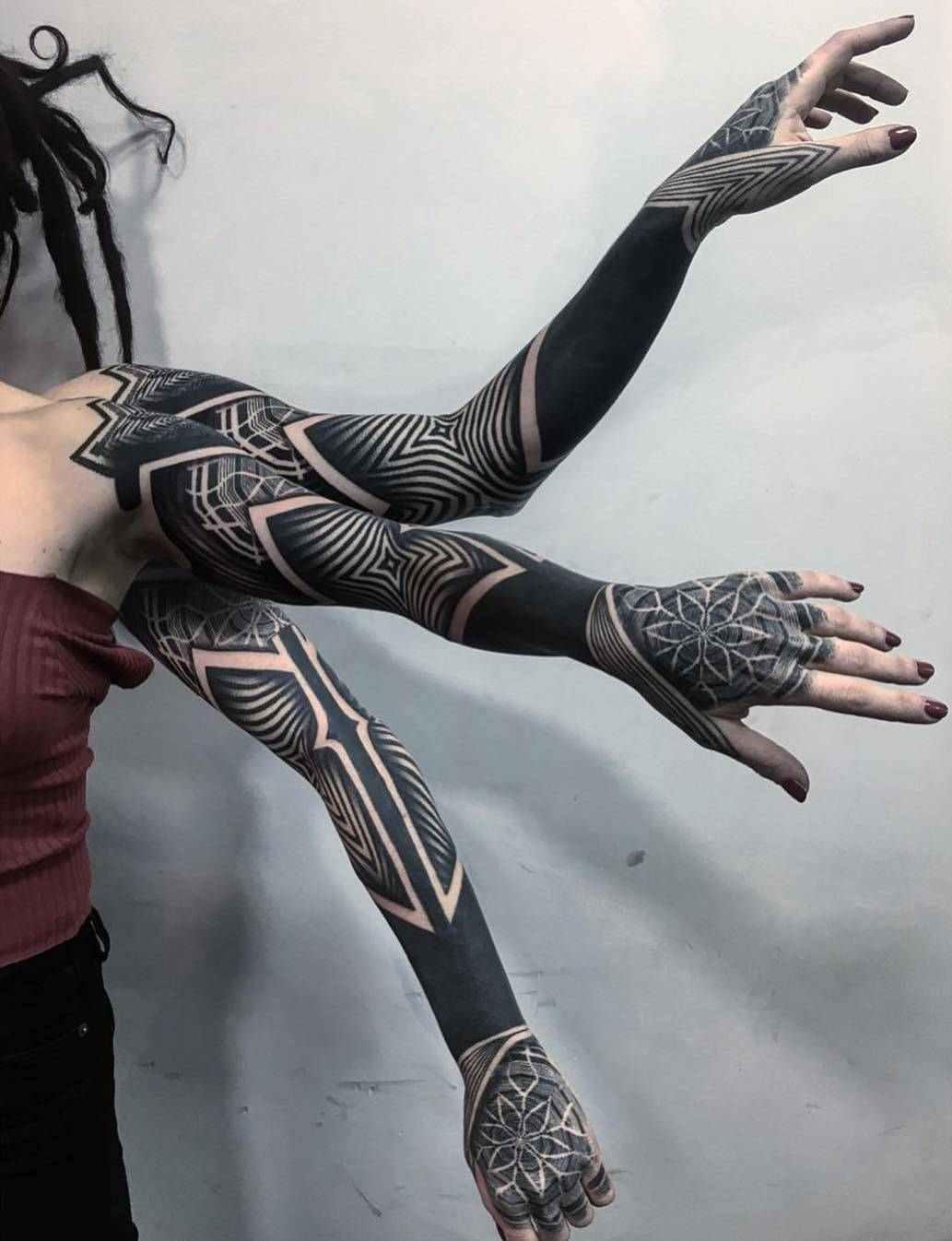 Un tatuaje geometrico en blanco y negro en el brazo de una mujer