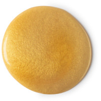 A circular pool of bright gold shimmery shower gel on a bright background