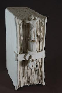 Escultura de cerámica de un libro con candados y una persona mirando en el interior