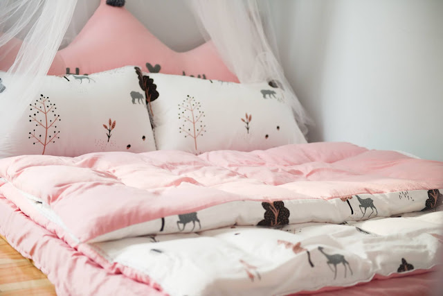 A girly bed spread in pink and white.
