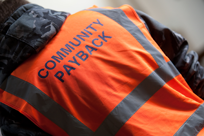 Man with back turned to camera wearing a hi-vis Community Payback tabard