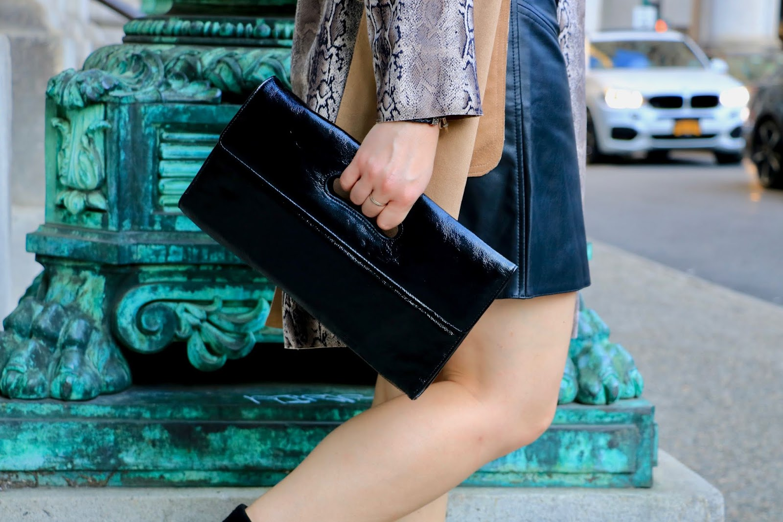 Nyc fashion blogger Kathleen Harper carrying a black patent leather clutch.