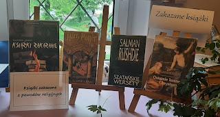 Na zdjęciu są 4 sztalugi a na nich 4 książki. Obok znajdują się dwa napisy. Pierwszy to; Książki zakazane. Drugi to: Książki zakazane z powodów religijnych.