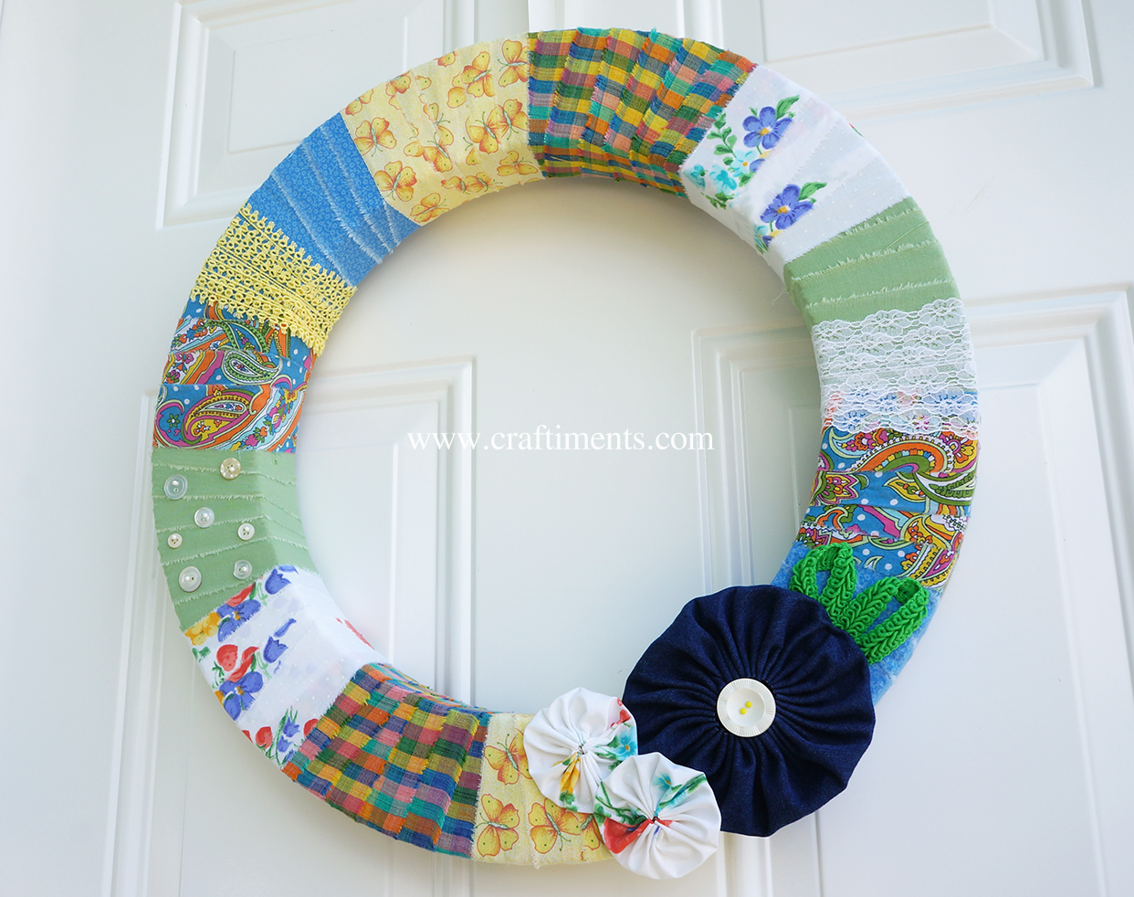 Styrofoam wreath wrapped with torn fabric strips, lace and trim, with buttons and yoyo fabric flowers