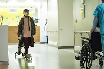 Movie still for the romantic drama Five Feet Apart where actor Moises Arias skateboards inside a hospital as he pulls his osygen tank