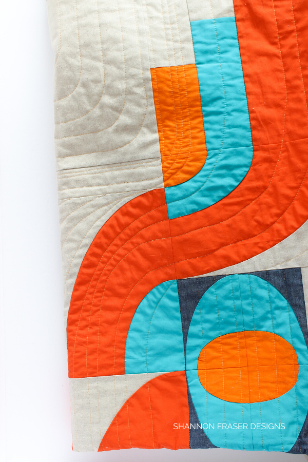 Quilting details on lap Cloud Surfing Quilt | Modern quilt pattern | Shannon Fraser Designs #modernquiltpattern #quiltingcurves #color