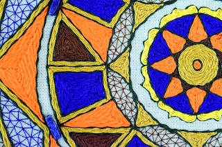 close up hand embroidered yantra