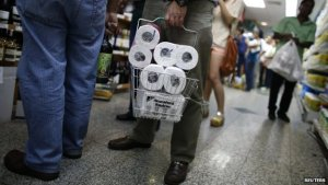 A view of people's legs as they are stand in line at a store. One man is holding a shopping basket full of toilet paper.
