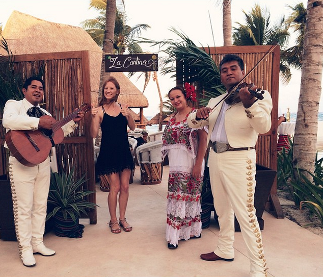 Men in charro suits with woman in Mexican garb before tequila tasting