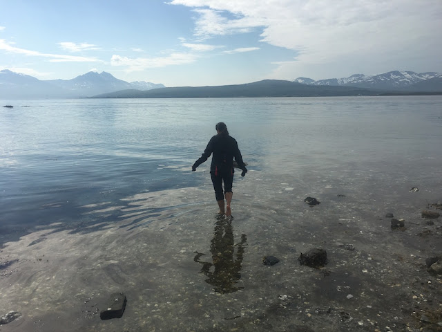 Picture of lone girl walking into the ocean with mountains in the background