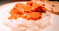 Serving Chicken tikka masala (murgh tikka masala) over steam rice with naan bread