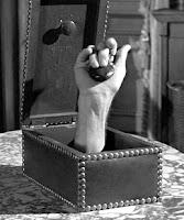 Fotografía del mayordomo de la mano-mascota de la familia Addams. En la imagen la mano sale de una caja y toca una castañuela