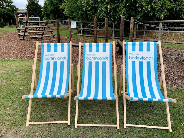"3 deckchairs saying ""we are barleylands"" and a play area in the background"