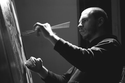 A painter is focused as his hands flick the brush over the canvas