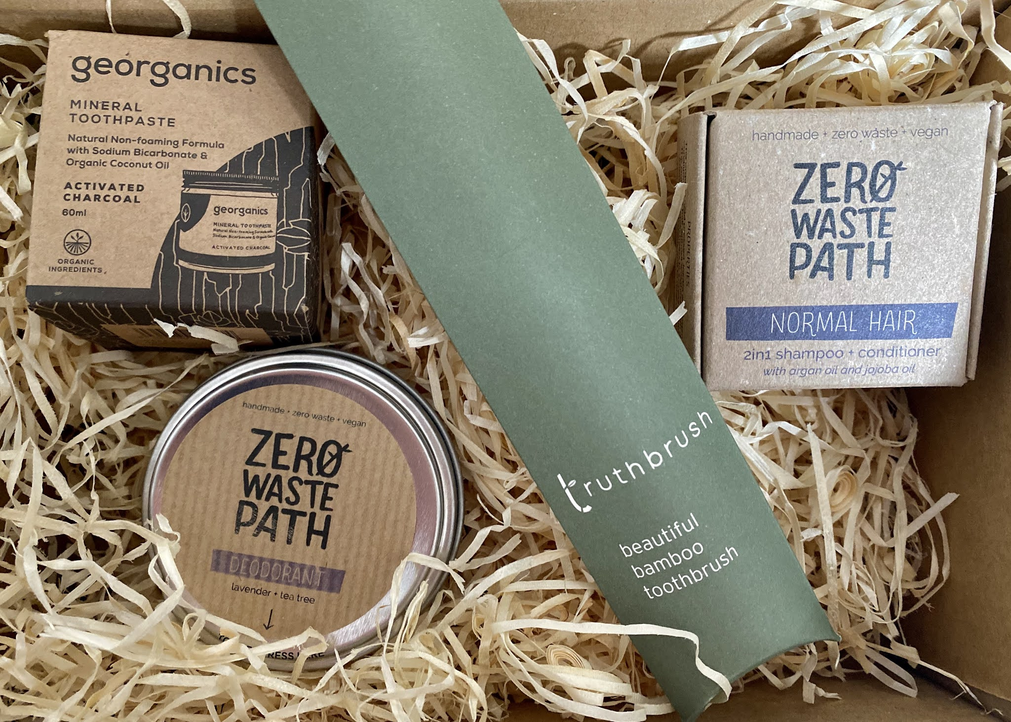 A delivery of eco products for the bathroom: a deodorant tin, jar of toothpaste, bamboo toothbrush and shampoo bar. All in their packaging