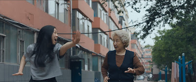 Awkwafina does tai chi with Shuzhen Zhao in a movie still for the A24 drama The Farewell