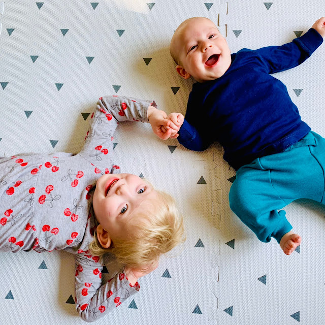 Little lying on some soft floor mats next to her baby brother, they are holding hands and both smiling