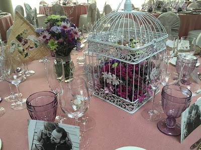 Jaulas llenas de flores y velas como centros de mesa en un banquete