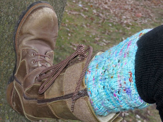 Someone wearing a sky blue boot topper knit in worsted yarn; with lace eyelets visible