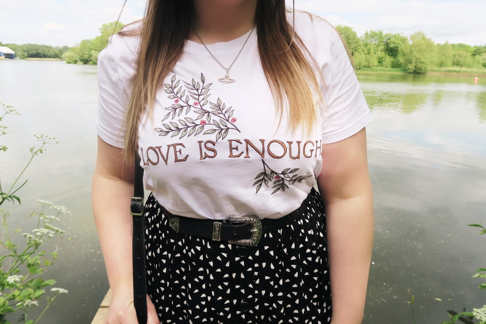 Close up of tshirt and embroidered detail which reads ''love is enough''