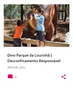 Duas crianças junto de uma estátua de estegossauro, a fazer-lhe festas