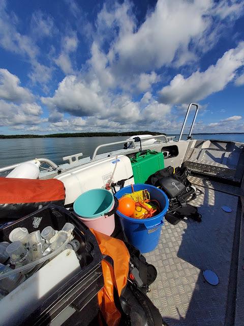 Kuva veneestä merelle, poutapilvinen taivas ja paljon tavaraa veneessä