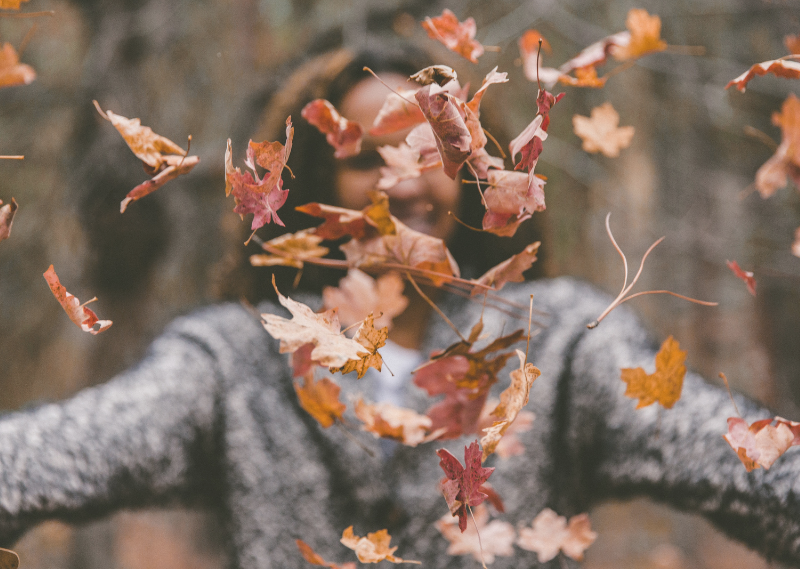 Lady throwing autumnal leaving in the air in a post about 20 things you can do before the end of 2020