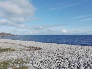 kameňová pláž s výhľadom na more, v pozadí kompa