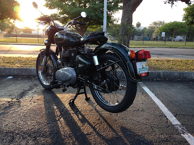 Motorcycle in parking lot as sun comes up.