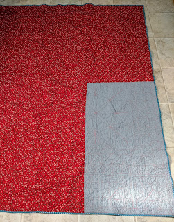 Red calico and grey solid form the quilt back