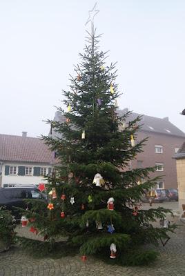 Ein festlich geschmückter Weihnachtsbaum steht vor der Kirche in Hülchrath