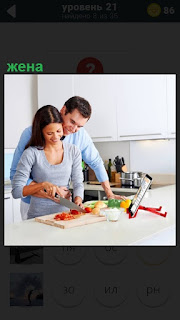 На кухне стоит жена и муж обнимает её за талию, которая готовит