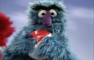 Herry Monster squishes the beach ball with his hands and the air of the beach ball out. Elmo's World Balls Home Video