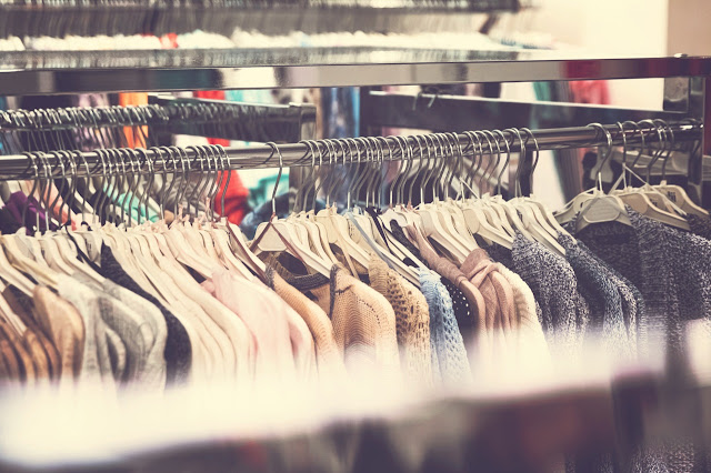foto de camisas dependuradas em cabides com a imagem embasada.