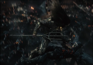 Aquaman standing on a Parademon's chest as he rides it downward through the sky.