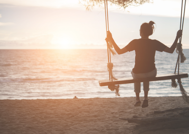 Girl sat on a swing facing the beach in a post about how we can live a more simple and intentional life