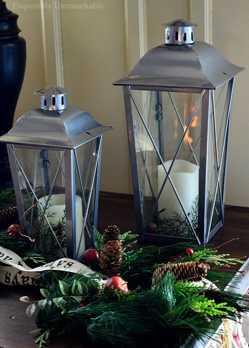 Silver Lanterns set on a table with evergreen wreaths for Christmas
