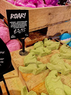 A pile of light green dinosaur shaped bath bombs on a square light brown box with a black rectangular table with roar! in white font on a bright background
