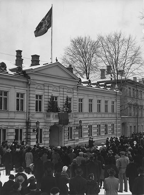 Ihmisjoukko vanhan rakennuksen edustalla talvella.
