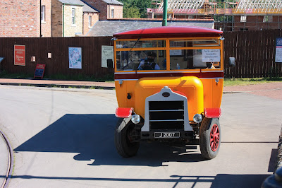 Photo of an old yellow omnibus, with a sign in the window saying wheelchair accessible vehicle.