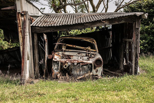 old wrecked car in collapsing garage
