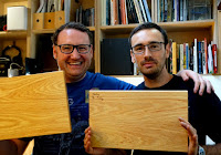 Image of two men each holding a chopping board.
