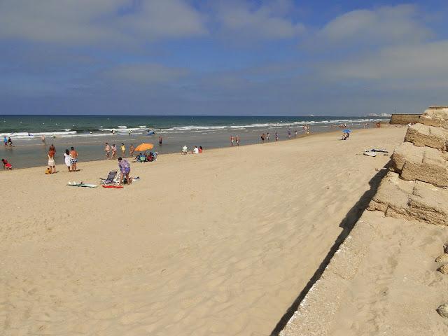 Playa de Cortadura con murallas de cortadura al fondo